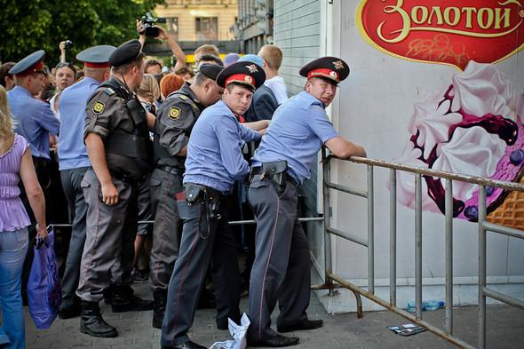 Полицейские ставят ограждения, но люди пытаются перепрыгнуть через них. Каждую преграду в итоге держат вчетвером.