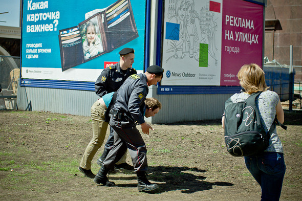 Несколько фотографов прорываются сквозь оцепление, чтобы снять задержание с выгодной точки. Полиция довольно решительно пресекает попытки прессы снять происходящее и старается запихнуть журналистов обратно за оцепление.