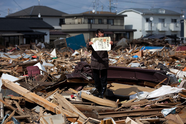 Ясуоси Тиба, Япония, Agence France-Presse. Жительница дома, разрушенного землятресением в Японии, держит в руках диплом своей дочери. Изображение № 13.