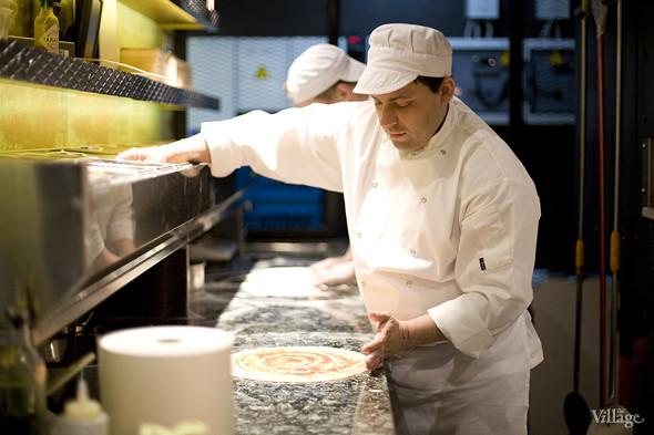 На основе для пиццы равномерно распределяют соус из томатов