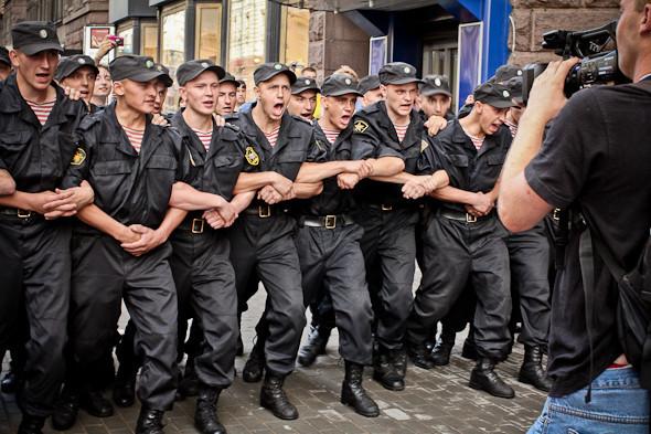 Всех активистов задержали, но люди не расходятся. Руководство полиции решает подключить солдатов. Они встают в несколько рядов и начинают устрашающе топать ногами и скандировать: Раз! Раз! Раз!. Изображение № 30.
