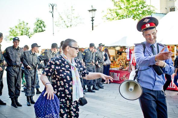 Страж порядка объясняет пожилой женщине, что лучше проследовать к метро, пока ее туда не оттеснили силой.